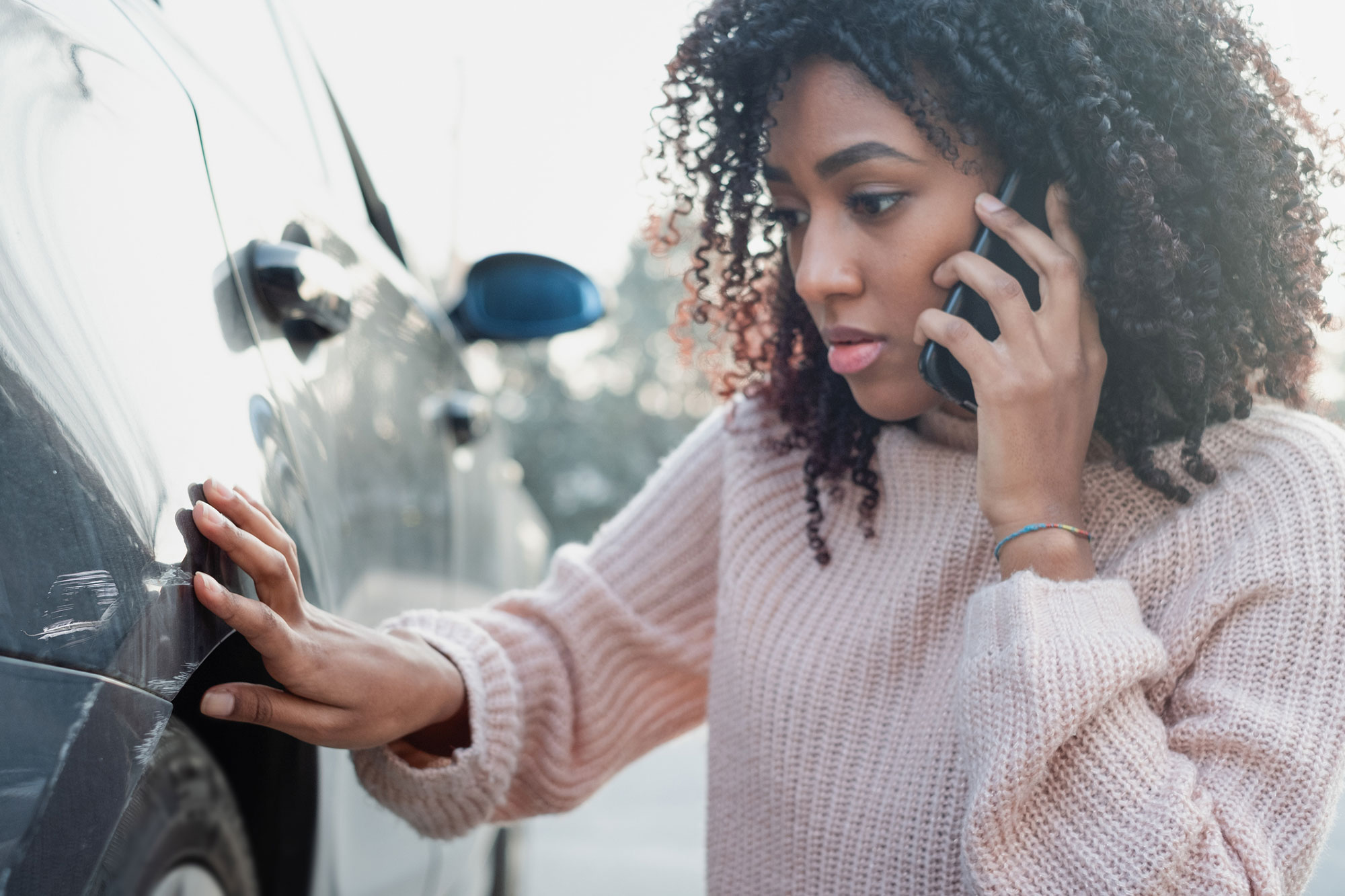 Woman on the phone looking at damage on the side of her car