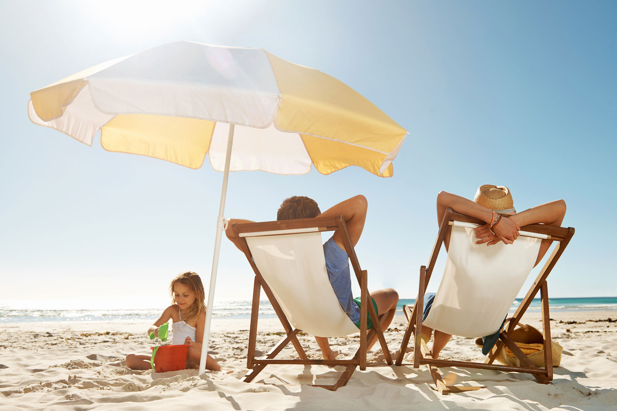 Family lounging on the beach in chairs with an umbrella blocking the sun